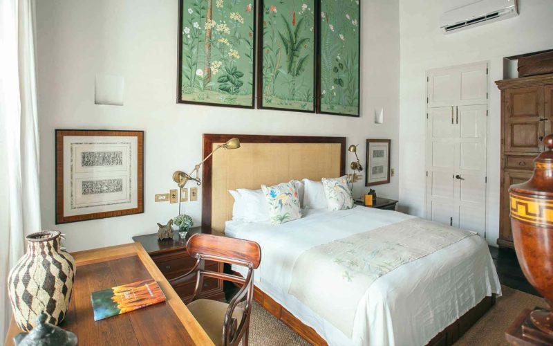 Habitación Macaw con cama en el centro, escritorio y silla cerca de la ventana