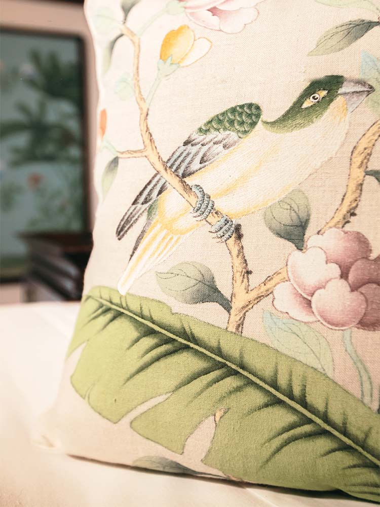 close up detail of embroidered pillow with parakeet