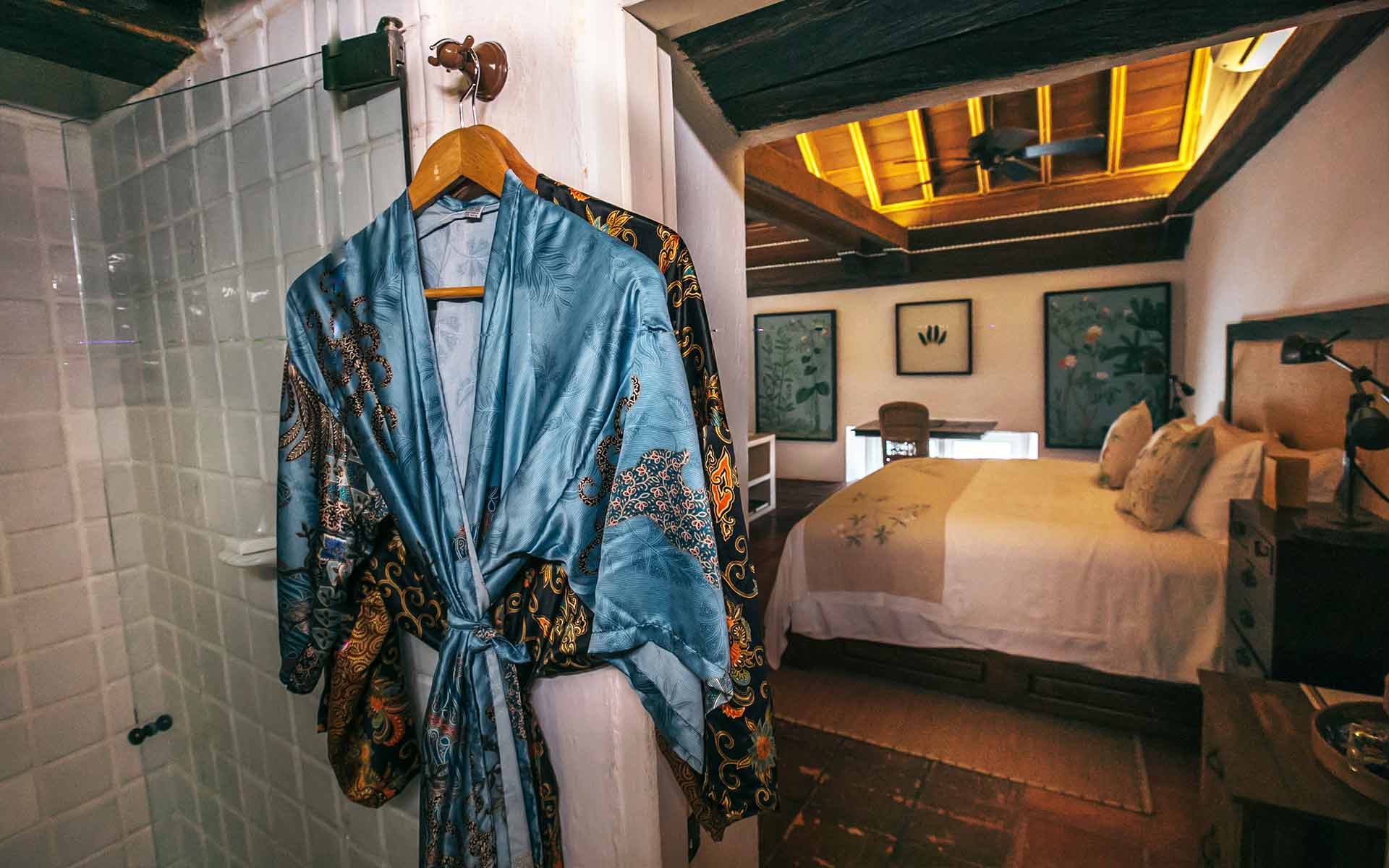view of bed with shower and two silk robes hanging in the foreground