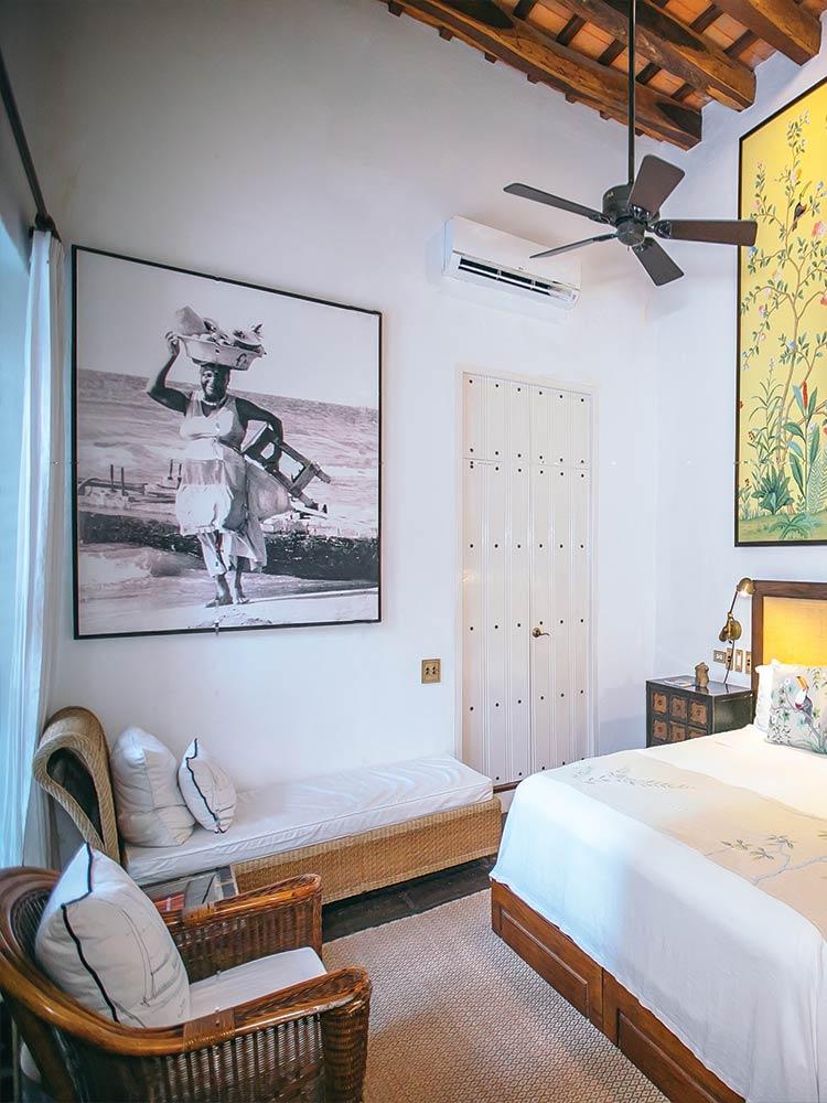 Habitación de tucán con piso de pasto marino y chaise lounge y obras de arte de Tucán amarillo del hotel Amarla