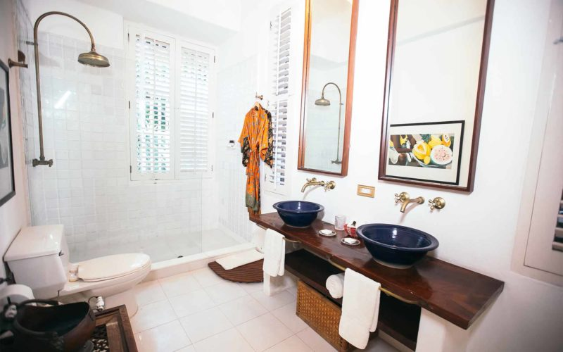 Bathroom with white floor tiles, twin blue freestanding basins and huge walk in white tiled shower