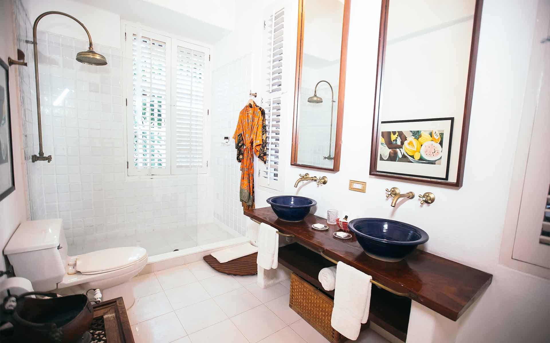 Cuarto de baño con baldosas blancas, dos lavabos independientes azules y una enorme ducha con baldosas blancas