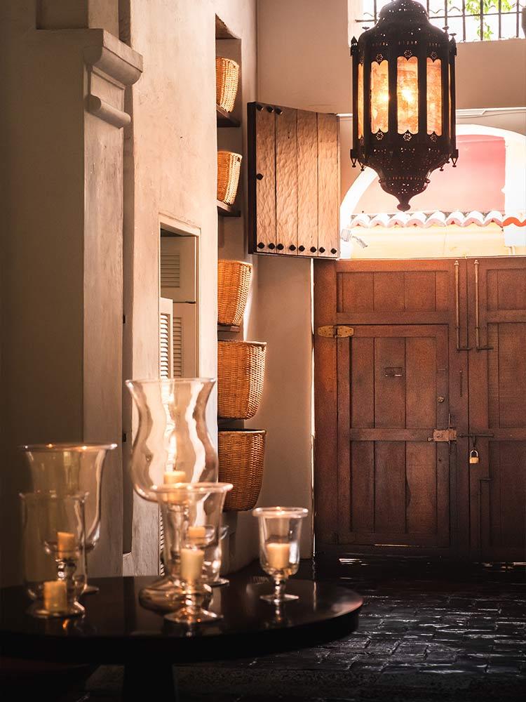 Entrada con enormes puertas de madera originales con luz natural y velas en el Amarla Boutique Hotel Cartagena Colombia