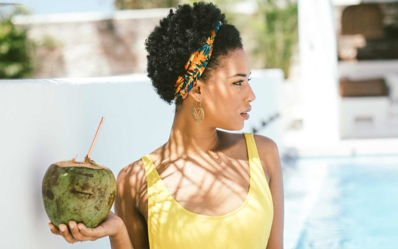 Stunning girl relaxing by the rooftop pool with fresh coconut juice at a Cartagena retreat held at the Amarla Boutique Hotel