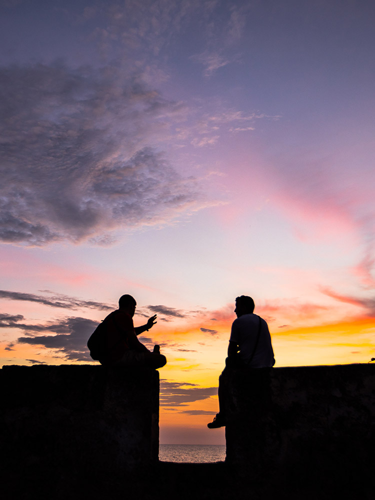 Two people sitting on the old city outer wall looking over the sea at the Cartagena sunset