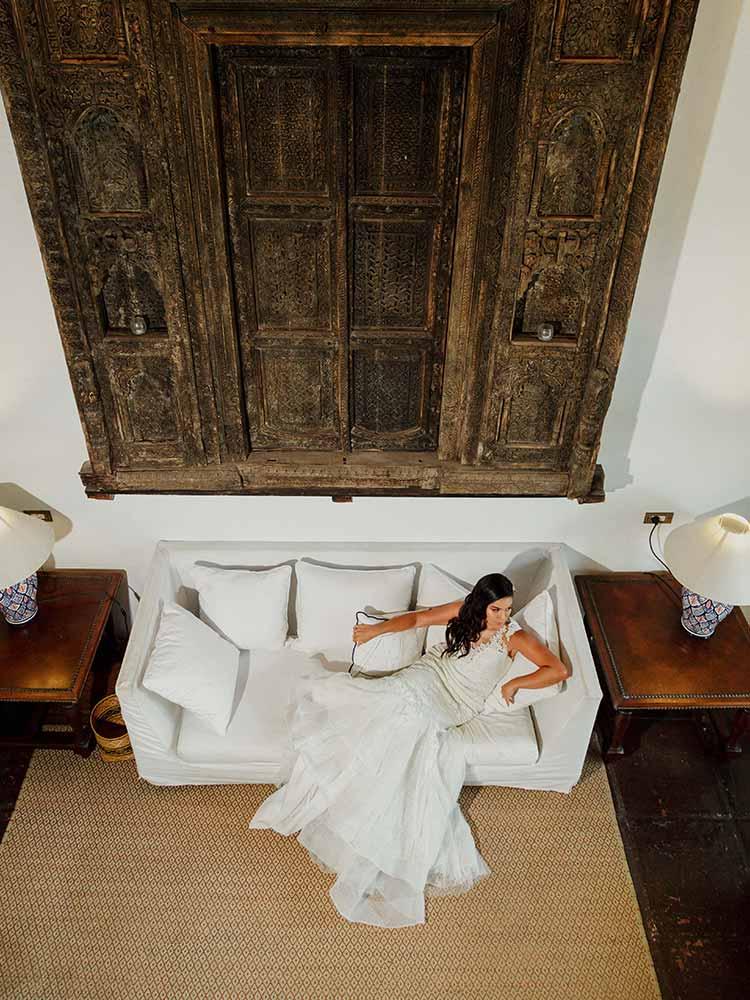 Novia en su fantástico vestido, relajándose en el sofá en el Hotel Amarla Cartagena en Colombia, ideal para celebrar matrimonios en Cartagena