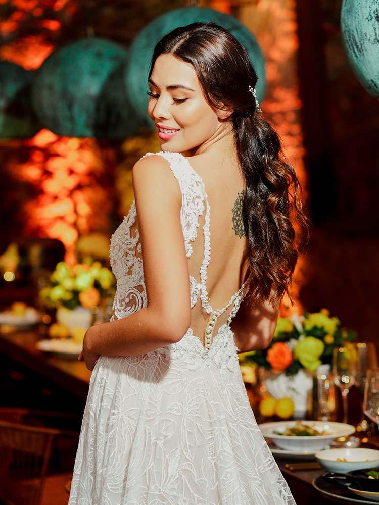 Novia revelando su espléndido tatuaje de mandala mientras luce un vestido escotado en la parte de la espalda mirando por encima del hombro, en su boda en Cartagena en Hotel Amarla