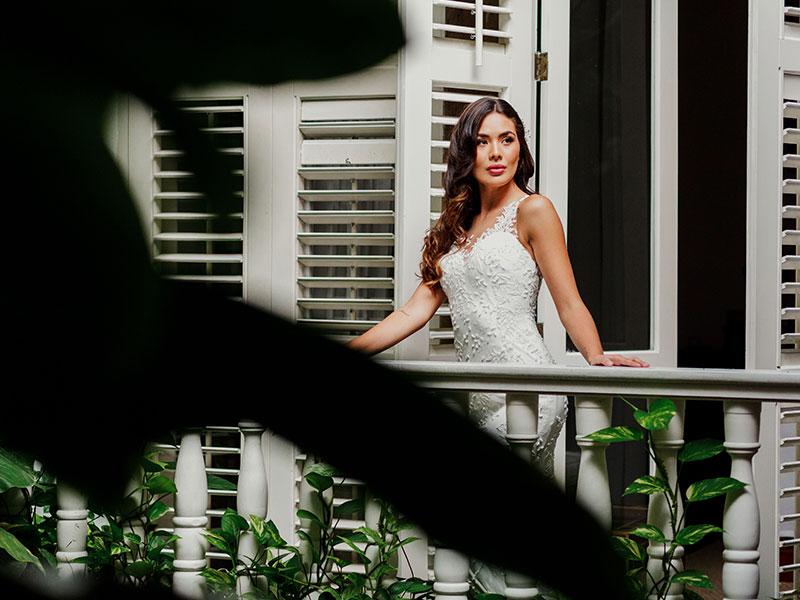 Bride on balcony overlooking Amarla inner courtyard and gardens before Cartagena wedding ceremony