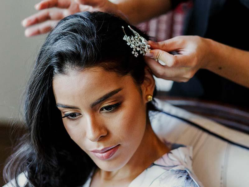 Novia dejandose dar los toques finales a su pelo en una de las bodas en Cartagena en el Hotel Amarla