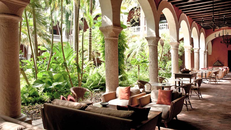 Lush courtyard with sofas, tables and chairs, from one of the best hotels in Cartagena