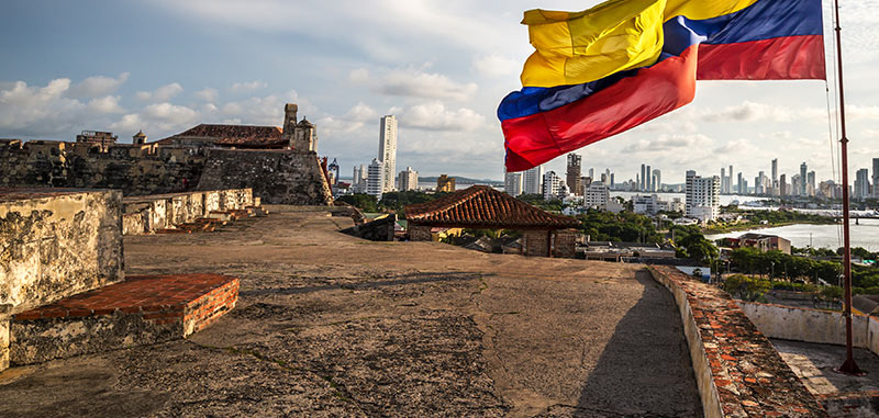 Colombian flag flying in the wind on the walls of the fort in Cartagena Walled City in Colombia